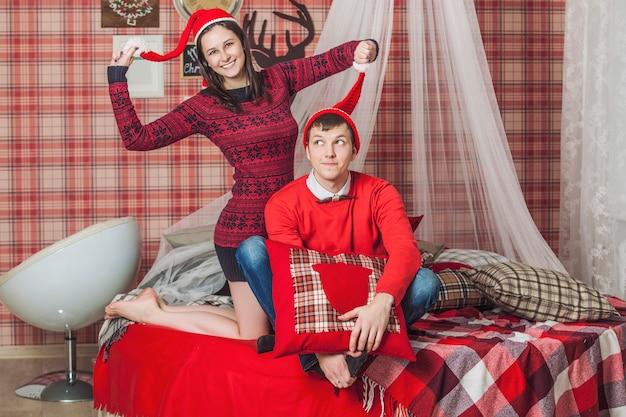 Coppia uomo e donna in camera da letto sul letto con una coperta nell'interno natalizio