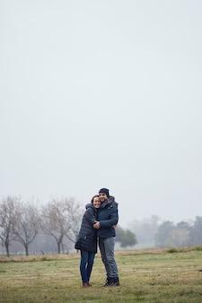 Coppia di uomo e donna che si abbracciano nel campo in inverno. donna bionda e uomo marrone.