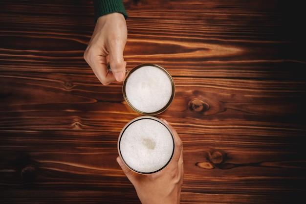 Coppia di uomo e donna o amici che tengono un bicchiere di birra per festeggiare in ristorante o bar, per l'oktoberfest o qualsiasi concetto di evento allegro, vista dall'alto sul tavolo di legno