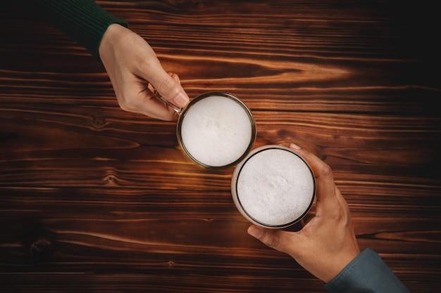 Coppia di uomo e donna o amici che tengono un bicchiere di birra per festeggiare in ristorante o bar