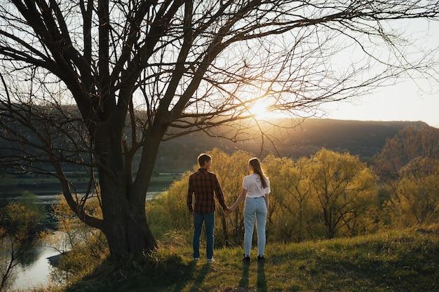 Coppia di uomo e donna che si tengono per mano, guardandosi e in piedi insieme sotto l'albero con la parete del cielo al tramonto.