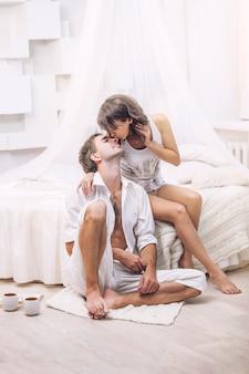 Coppia uomo e donna a casa a letto con una tazza di caffè. tenero amore nelle relazioni familiari