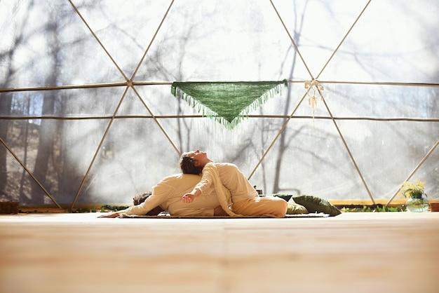 Coppia di un uomo e di una donna a praticare yoga tantrico in una cupola geodetica