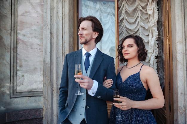 Coppia, uomo e donna, con champagne sul balcone del palazzo storico in abiti da sera, completo e vestito. una coppia di anziani innamorati trascorre il fine settimana. concetto di appuntamenti romantici e sorprese. copia spazio