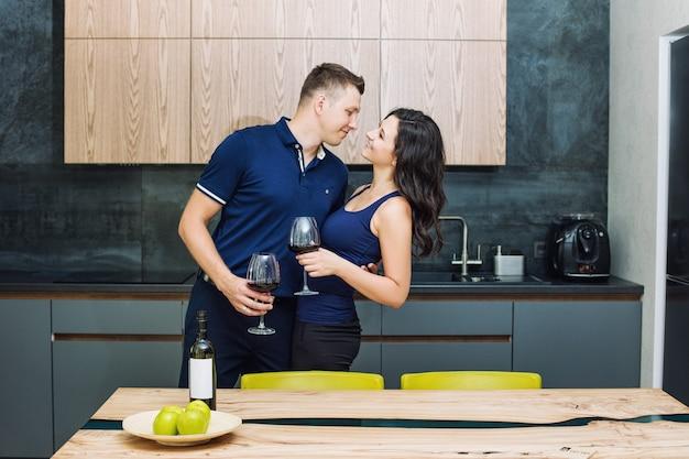 Coppia uomo e donna giovane bella e felice in cucina con bicchieri winan