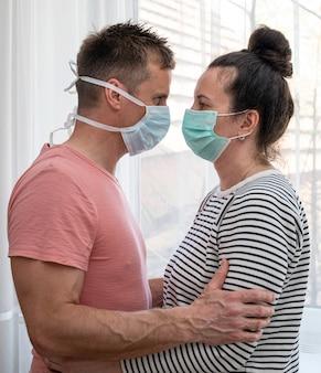 Coppia in maschere mediche in posa a casa durante la quarantena