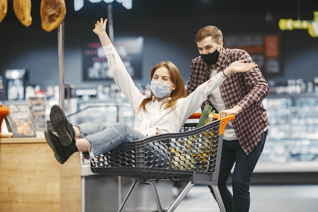 Coppia in maschera protettiva medica in un supermercato.