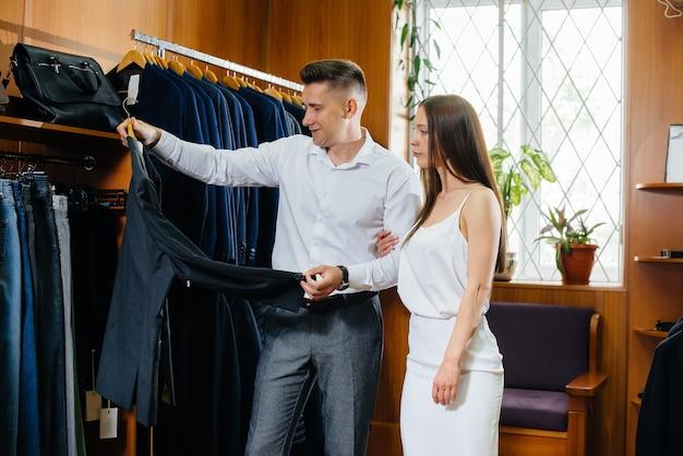 Un paio di uomini e donne scelgono i vestiti nel negozio.