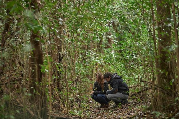 Coppia di mezza età caucasica uomo e donna sorridente esaminandosi nella foresta, tra foglie e rami degli alberi in inverno.
