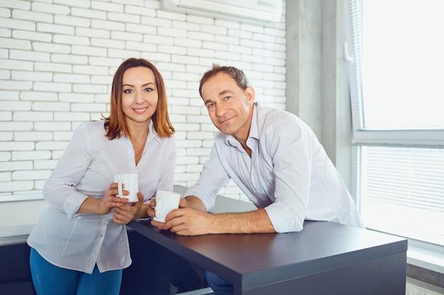 Un paio di persone di mezza età con tazze in mano in casa