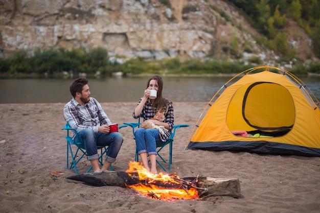 Coppia vicino al fuoco di campo in fase di riscaldamento visto dalla tenda