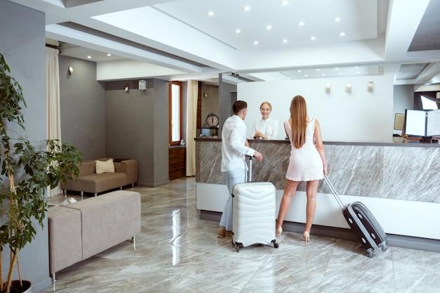 Le coppie si avvicinano alla reception in hotel