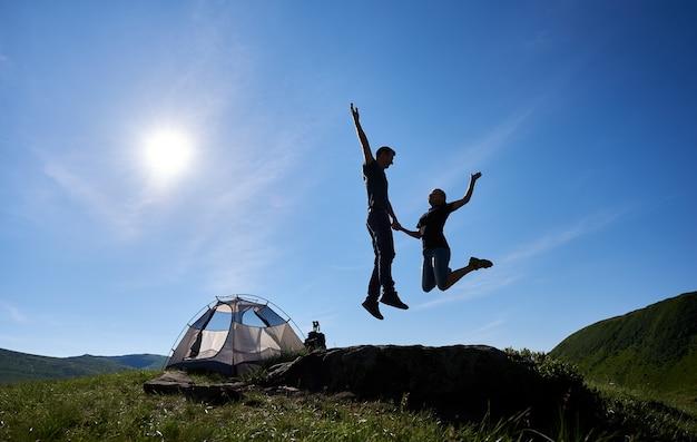 Coppia vicino alla tenda turistica in montagna