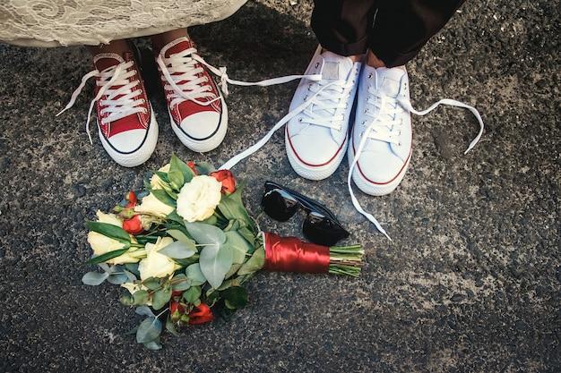 Coppia di nuovi matrimoni con divertenti scarpe da ginnastica uguali e bouquet da sposa, occhiali da sole. dettagli del matrimonio.