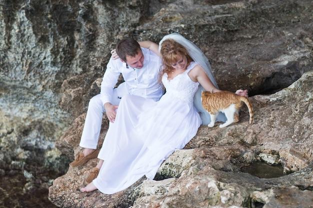 Coppia sposi novelli sposi con gatto, momento felice e gioioso.