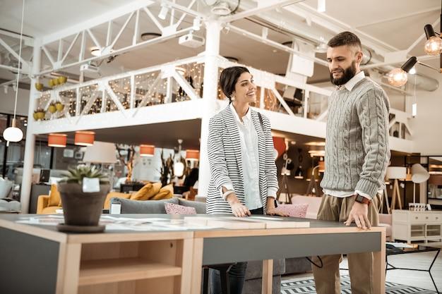 Coppia osservando la qualità. coppie allegre piacevoli che discutono attivamente le caratteristiche del tavolo necessario mentre si trovava nello showroom