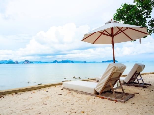 Lettino da esterno di coppia con vista sul mare. due lettini in legno vuoti con sedili in tessuto con ombrellone sulla spiaggia di sabbia con isola, mare, nuvole e cielo blu con spazio per le copie. Foto Premium