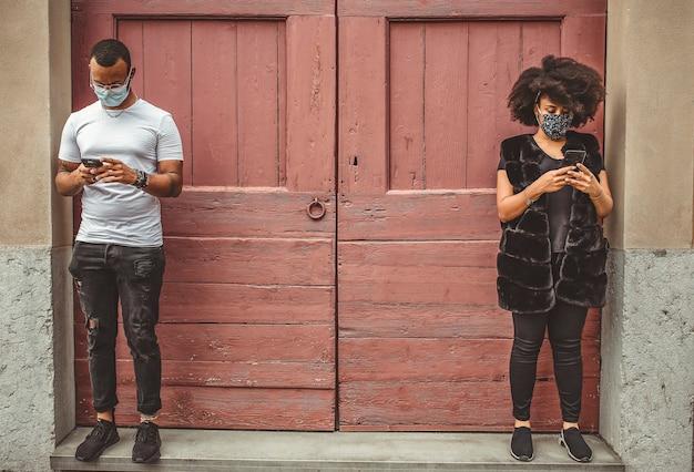 Coppia all'aperto indossando maschere con cellulare