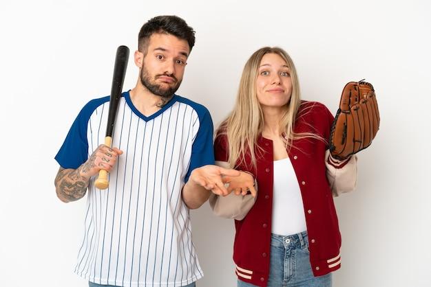 Coppia che gioca a baseball su sfondo bianco isolato avendo dubbi mentre alza le mani e le spalle