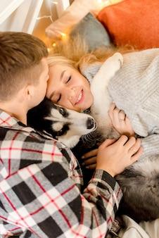 Coppie che giocano con il cane in camera da letto