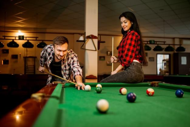 Coppia gioca nella sala da biliardo, giocatore di sesso maschile che mira