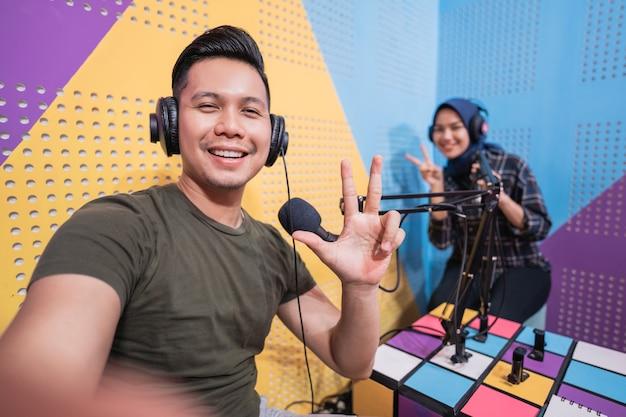 Coppia in studio podcast che si fa un selfie con il telefono insieme
