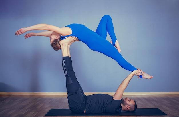 Coppia pratica acroyoga insieme. coppia pratica acro yoga in uno studio bianco.
