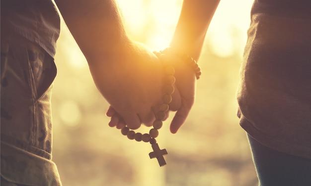 Coppia che prega insieme. tenendo in mano il rosario.