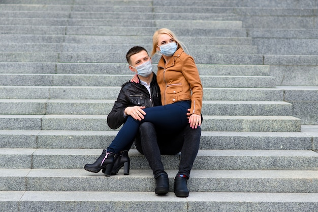 Coppia in maschere protettive fare una passeggiata all'aperto in città vicino a un edificio commerciale in fase di quarantena. concezione del coronavirus.