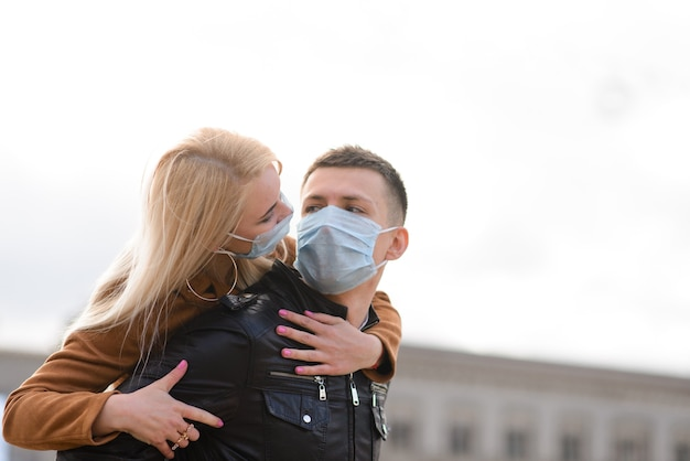 Coppia in maschere protettive fare una passeggiata all'aperto in città vicino a edificio commerciale in fase di quarantena