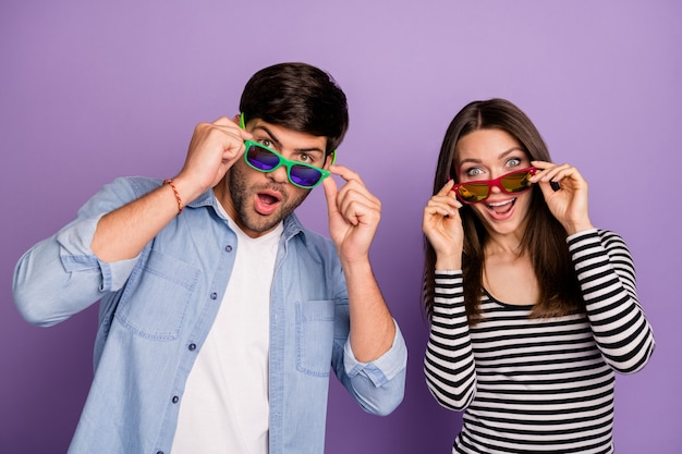 Coppia lettura felicissima indossare occhiali da sole e abbigliamento casual isolato muro di colore viola