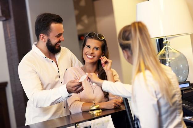 Coppia e receptionist al bancone in hotel