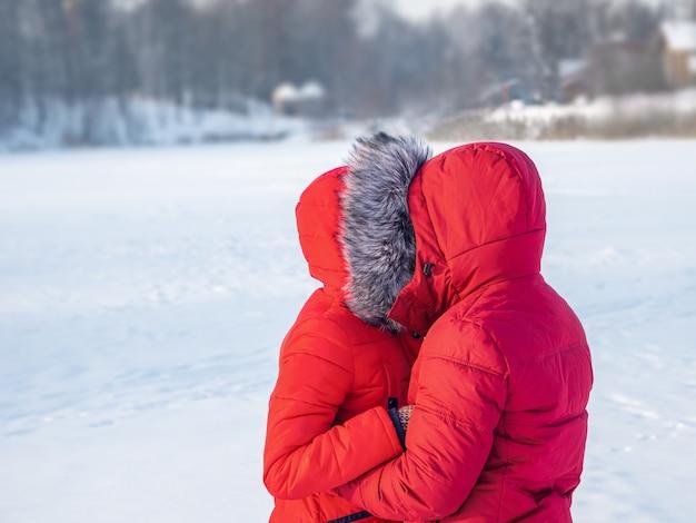Una coppia in giacche rosse in inverno si abbraccia al freddo.