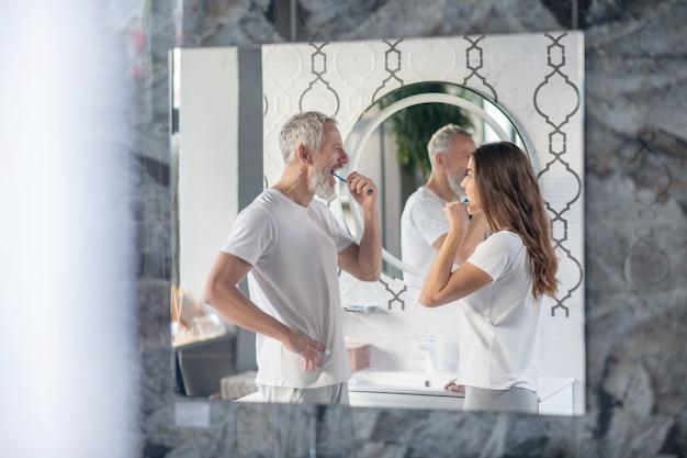 Coppia, relazione. profilo riflettente nello specchio dell'uomo e della donna lavarsi i denti uno di fronte all'altro nella mattina in bagno
