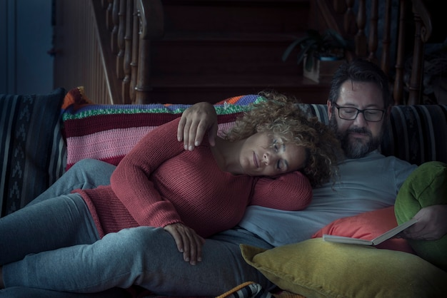 La coppia si rilassa a casa di notte con una donna che dorme e un uomo che legge un libro insieme sul divano