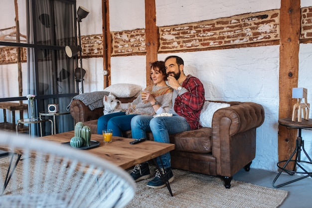 Coppia rilassata a casa sul divano a guardare la tv e mangiare popcorn
