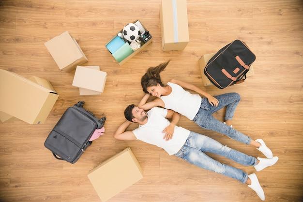 La coppia riposa sul pavimento vicino a scatole di cartone. vista dall'alto