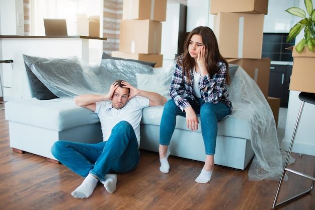 Coppia di riposo sul divano dopo essersi trasferito, uomo e donna che si rilassano sul divano appena trasferito nell'appartamento con scatole di cartone sul pavimento, proprietari di case stanchi e sconvolti e primo giorno nella nuova casa