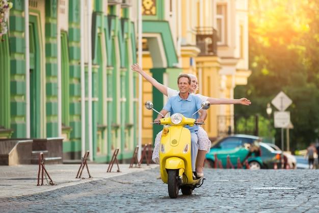 La coppia guida il motorino giallo.