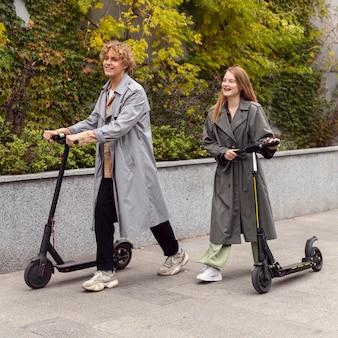 Coppia in sella a scooter elettrici insieme