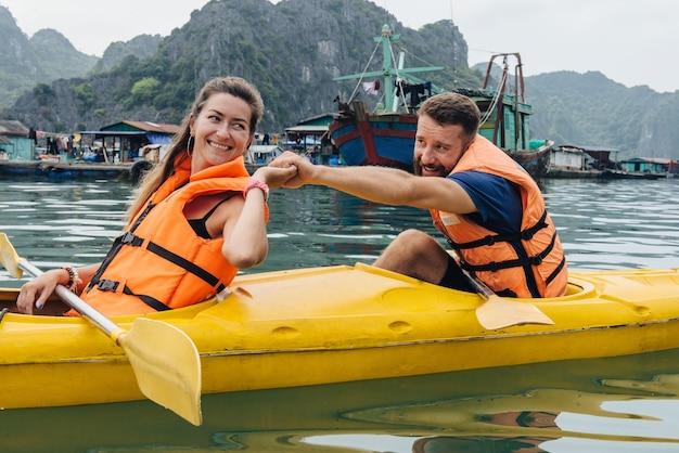 Coppia kayak a remi e si sostengono a vicenda nella baia di ha long. persone felici che esplorano la natura.