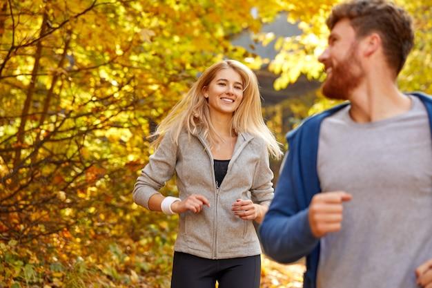 Le coppie corrono insieme nella foresta di autunno, l'uomo sportivo atletico e la donna in abiti sportivi si divertono a fare jogging all'aria aperta, in una giornata di sole