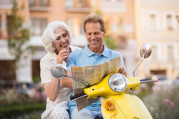 La coppia sul motorino sta sorridendo.