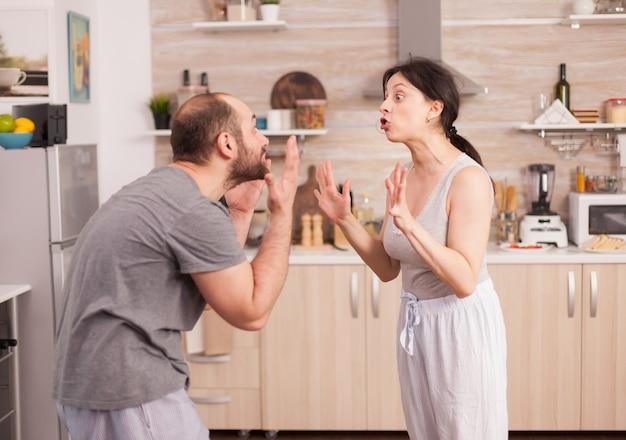 Coppia urlando a vicenda in cucina al mattino. la giovane coppia litiga in cucina. l'uomo e la donna urlano frustrati durante la conversazione domestica.
