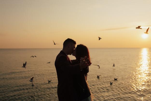 Coppia sulla spiaggia del mare si bacia durante il tramonto
