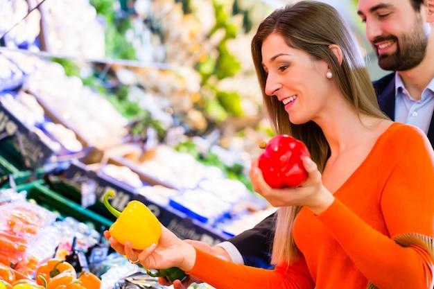 Coppie che selezionano le verdure nell'ipermercato