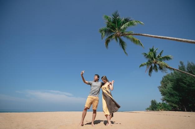 Coppia selfie sotto la palma da cocco sulla spiaggia sabbiosa con cielo blu.