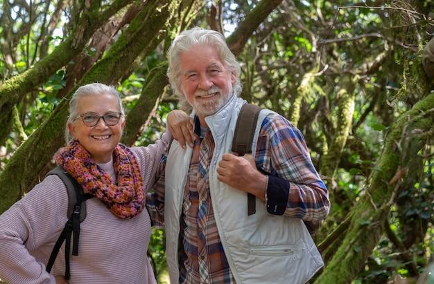 Coppia di uomini e donne anziani che si godono un'escursione in montagna nei boschi tra tronchi e rami ricoperti di muschio durante la stagione autunnale - concetto di anziani in pensione divertenti e attivi