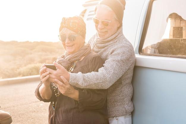 Coppia di anziani anziani viaggiatori caucasici che scattano foto al telefono selfie o fanno una conferenza con amici o genitori in piedi al tramonto con furgone vintage in backgorund - concetto di vita insieme