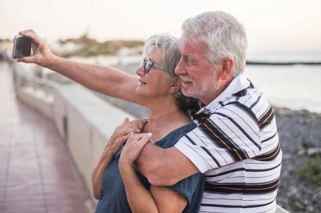 Coppia di anziani in spiaggia che scattano una foto insieme - donna con gli occhiali e uomo in pensione - selfie sulla spiaggia - divertirsi e divertirsi - caucasico 602